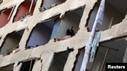 A woman looks out from a damaged building after a suspected car bomb in Diyarbakir on November 4.