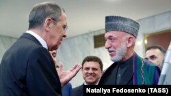 Russian Foreign Minister Sergei Lavrov (left) and former Afghan President Hamid Karzai talk at a meeting dedicated to the 100th anniversary of official Russian-Afghan diplomatic relations in Moscow on May 28.