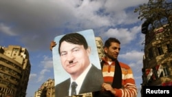 A protester holds a placard depicting Egyptian President Hosni Mubarak as Adolf Hitler in Cairo's Tahrir Square on January 31.