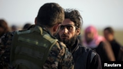 A fighter from Syrian Democratic Forces (SDF) checks a man near the village of Baghuz on February 22.