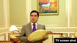 Қауын ұстап тұрған Түркіменстан президенті Гурбангулы Бердімұхамедовтың телеэкраннан түсірілген суреті.