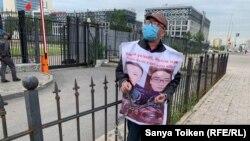 Житель Алматы Женис Заркын с плакатом с фото своих родственников приковал себя к ограде у посольства Китая. Нур-Султан, 26 июня 2020 года.