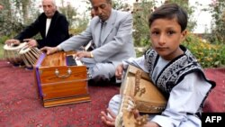 A young boy in Kabul plays a rabab, a traditional musical instrument.