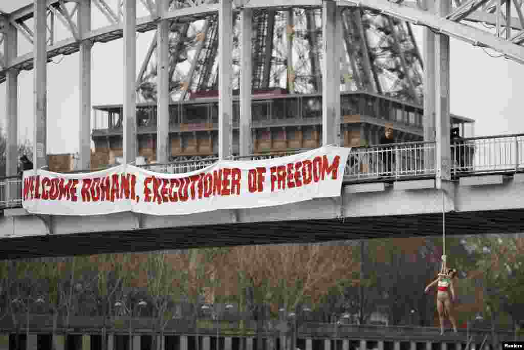 A topless Femen activist hangs from a bridge as the women's rights group stages a protest against Iranian President Hassan Rohani's visit to Paris on January 28. (Reuters/Charles Platiau)