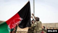 Авганистански и американски војници го креваат знамето на Авганистан на церемонија за прослава на Денот на авганистанската армија.