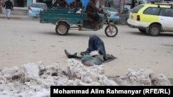 شریفه یکی از زنان گدا در جادهای در شهر شبرغان