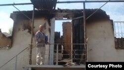 Азимжан Аскаров на фоне сгоревшего во время беспорядков дома. Базар-Коргонский район. Июнь 2010 года. Фото из семейного архива Аскаровых.