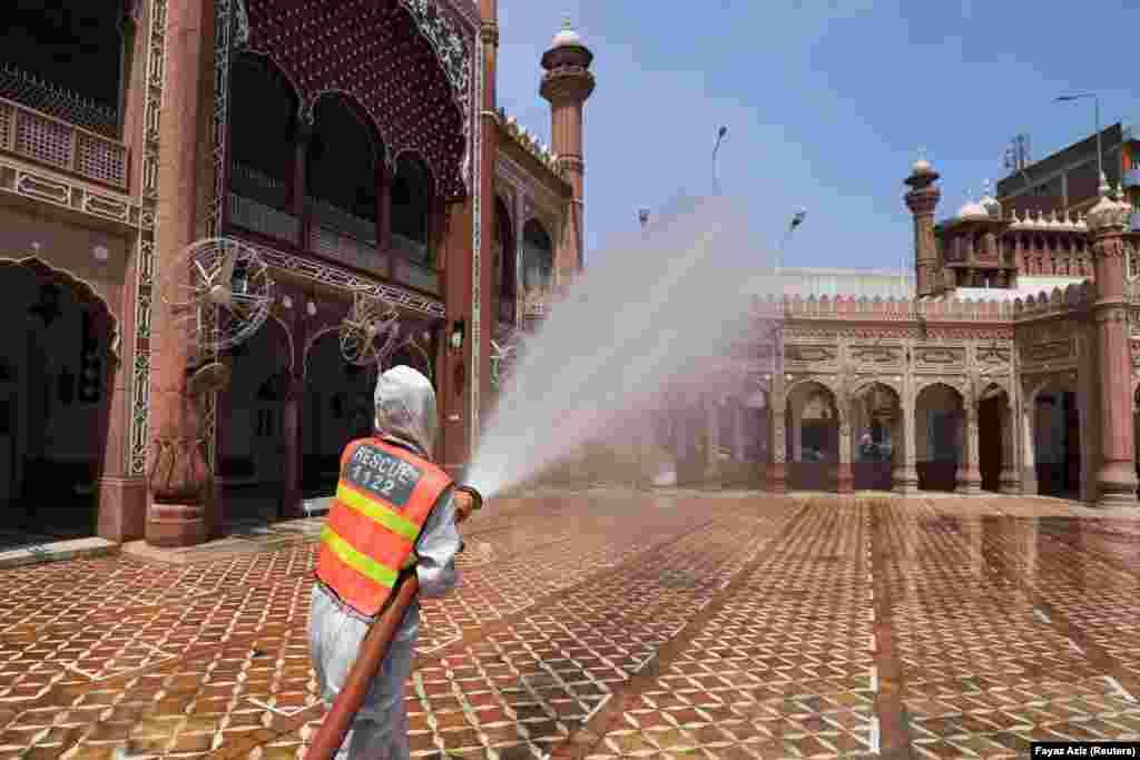 Рабочий дезинфицирует территорию мечети в Пешаваре, Пакистан. 13 апреля 2021 года.