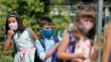 Alegra Bajrami (left), wearing a face mask to protect against the coronavirus, enters a schoolyard on the first day of the new academic year in Kosovo's capital, Pristina. Kosovar schools reopened on September 14 for the first time since March when the COVID-19 crisis began.
