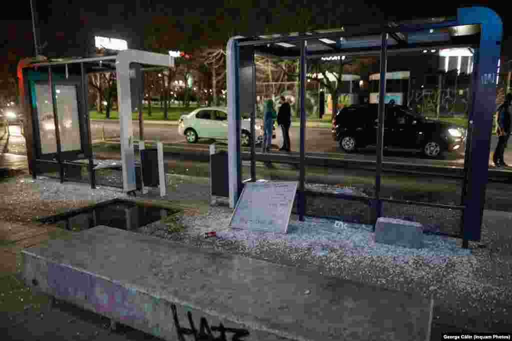 Broken glass is seen at a bus stop after stones were thrown by protesters.
