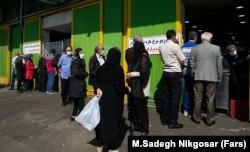 Люди в медицинских масках стоят в очереди за курицей в Тегеране. 5 апреля 2021 года