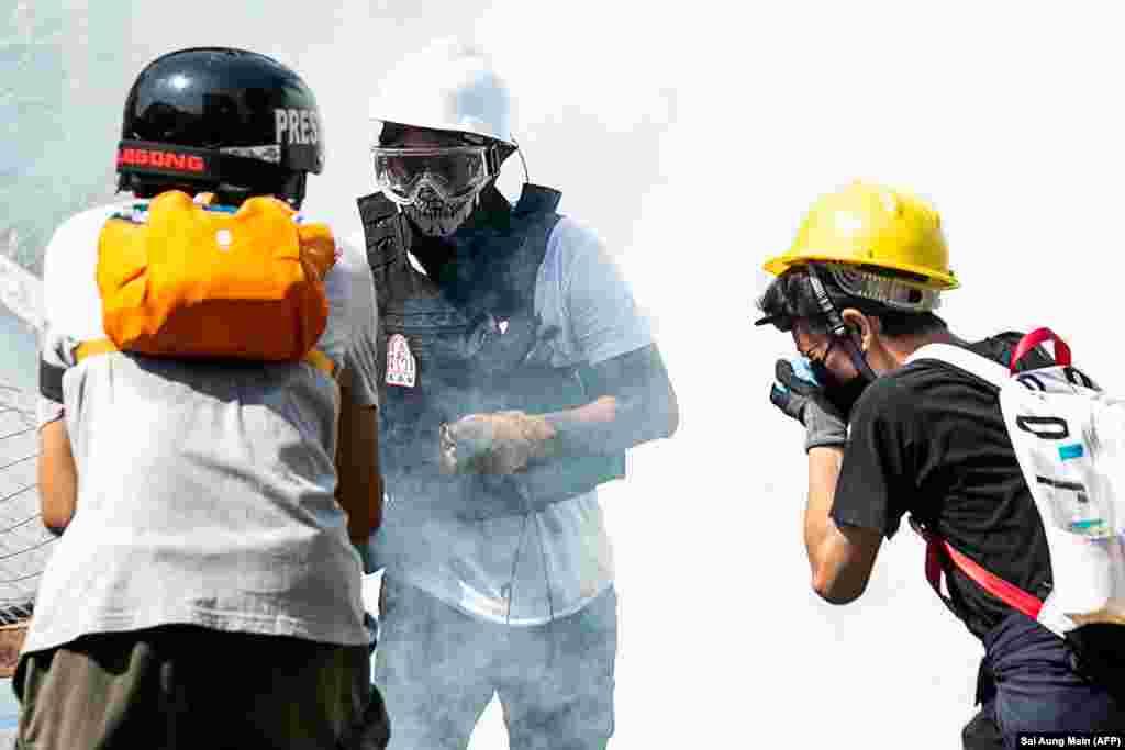 Протестувальники захищаються від сльозогінного газу, за допомогою якого сили безпеки придушують демонстрації проти військового перевороту в Янґоні, 28 лютого 2021 року