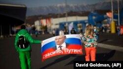 """Двама души държат руски флаг с образа на руския президент и с надпис """"Благодаря, Путин!"""". Снимката е от 2014 г."""