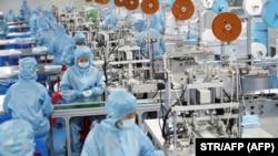 Védőöltözetet viselő munkások maszkokat gyártanak Lienjünkang városában, Kína keleti, Csiangszu tartományában 2020. október 29-én.