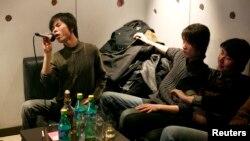 Группа друзей поет в местном караоке-клубе во время вечеринки в Шанхае 23 февраля 2008 года.