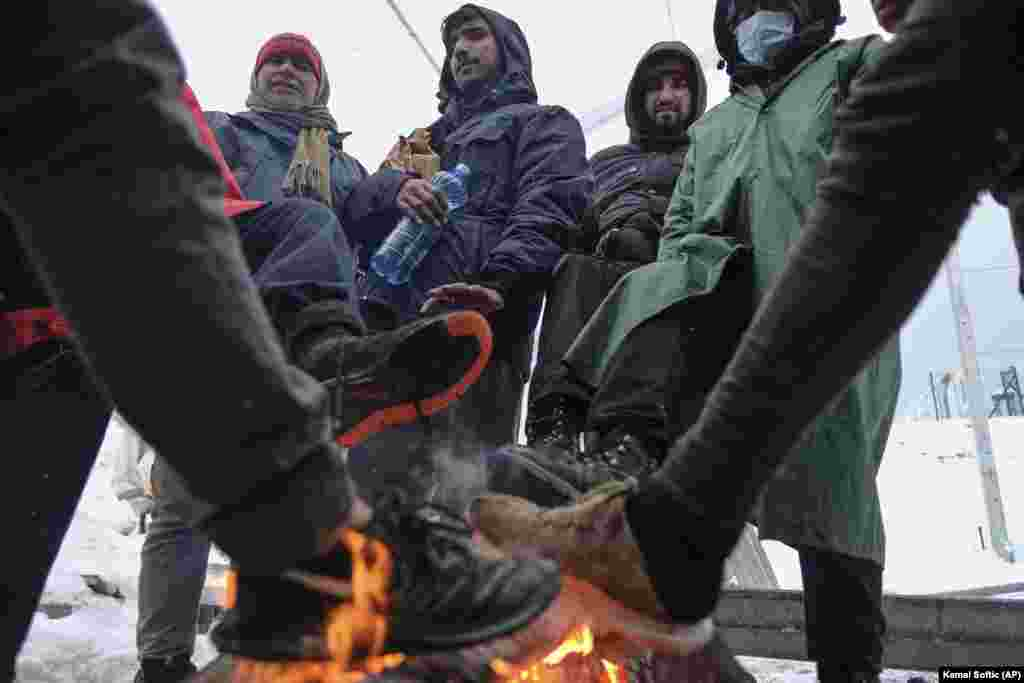 Migrants warm their feet by a fire at the camp.