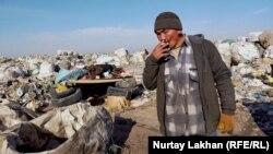 Мужчина, зарабатывающий на жизнь, разбирая мусор на полигоне в Алматы.