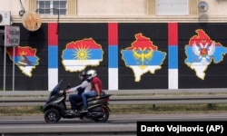 A motorbike passes a mural depicting (from left) the maps of Bosnia, North Macedonia, Kosovo, and Montenegro painted in the colors of the Serbian flag, in Belgrade on August 26.