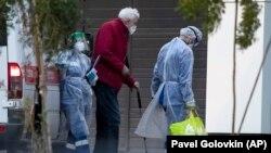 Медицинские работники в защитных костюмах помогают пожилому мужчине, страдающему COVID-19, выйти из машины скорой помощи в больнице в Коммунарге, за пределами Москвы, 29 сентября 2020 года.