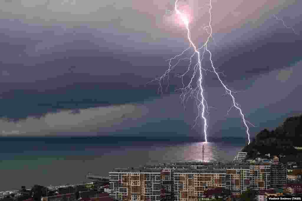 Un fulger este surprins deasupra Mării Negre, în largul stațiunii Dagomys din districtul Lazarevsky, Sochi.
