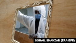 A worker wearing a face mask and a protective suit prepares coffins that are later distributed to hospitals to transport people who have died of the coronavirus.
