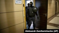 Russian police are shown raiding the offices of Aleksei Navalny's Anti-Corruption Foundation in Moscow on July 17.