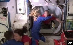 На этом кадре, сделанном по телевидению НАСА, астронавт Соичи Ногучи (на заднем плане справа) приветствует астронавта Кейт Рубинс, когда он входит на Международную космическую станцию из вестибюля между капсулой SpaceX Dragon и МКС ранним вторником, 17 ноября 2020 года.