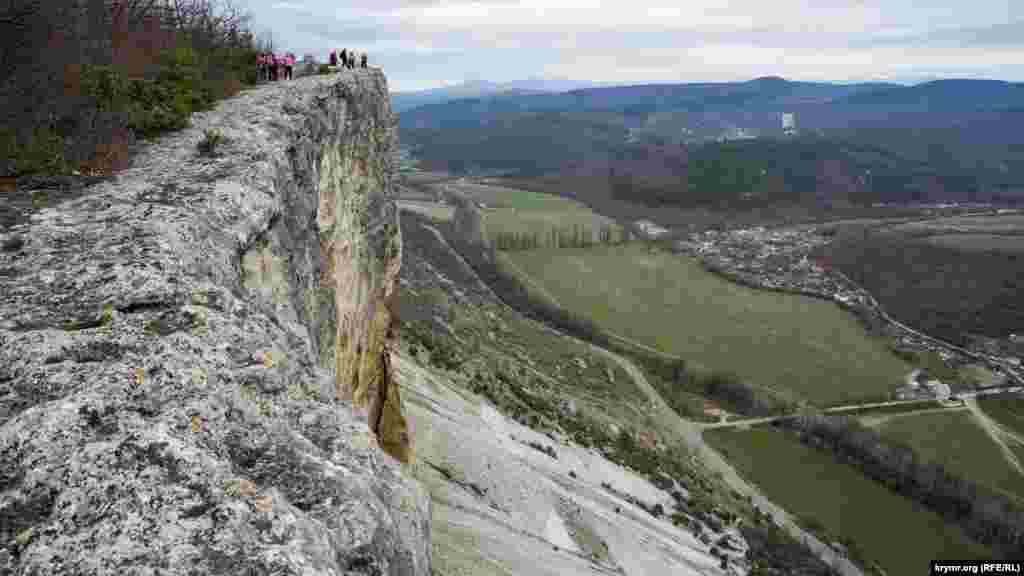 Туристи спостерігають за бейсджамперами з сусіднього мису, який на плато трохи південніше
