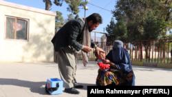 یک خانم در جوزجان کودکش را برای گرفتن واکسین پولیو به یکی از مراکز صحی آورده است.
