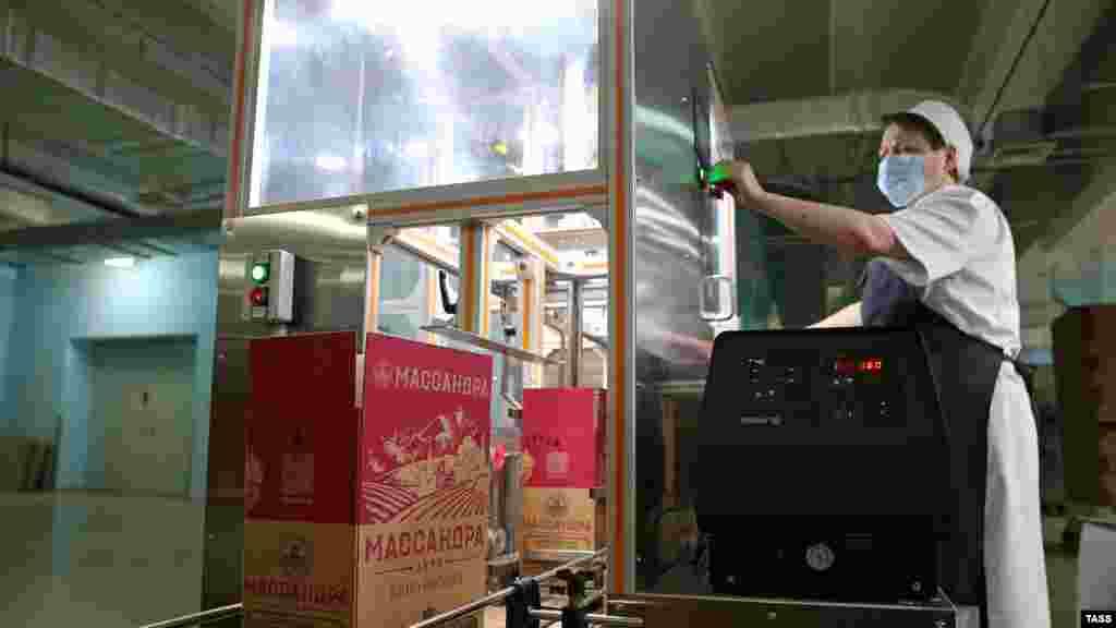 Оператор конвейера контролирует процесс упаковки бутылок вина