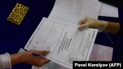 A woman receives her ballot paper at a polling station in Vladivostok on June 25.