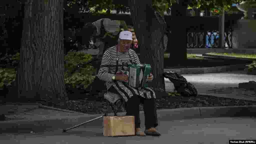 Вуличний музикант з гармошкою