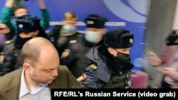 Москвоская полиция среди муниципальных депутатов, собравшихся на свой форум. На первом плане - оппозиционный политик Владимир Кара-Мурза