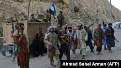 Afghan resistance forces patrol a road in Rah-e Tang, Panjshir Province, on August 29.