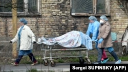 Ukrainian medical workers carry a body on a stretcher from a hospital to the morgue in Kyiv last week amid a wave of deaths and hospitalizations due to COVID-19.