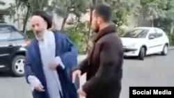 تصویری از ویدئو کلیپ سیلی زدن یک جوان معترض به فردی که لباس روحانی به تن دارد