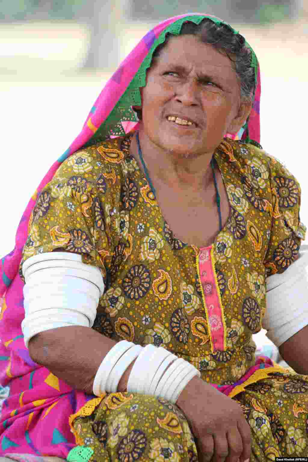 """Kallan Bibi, 50, says she has never left the area and does not like to travel by car, bus, or truck. """"I am happy here, but the heat wave is very strong these days and I am also getting old,"""" she says."""