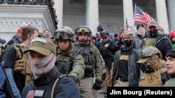 Jessica Marie Watkins (balról a második) and Donovan Ray Crowl (középen) és az Oath Keepers (eskütartók) szélsőjobboldali milícia más tagjai a Capitoliumnál 2021. január 6-án. A 2009-ben alapított milícia döntően a fegyveres szervek egykori tagjai közül próbál toborozni.