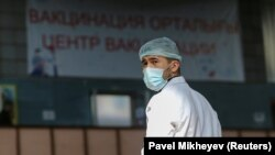Продавец в маске на рынке в Алматы. На заднем фоне надпись: «Центр вакцинации». 14 апреля 2021 года.