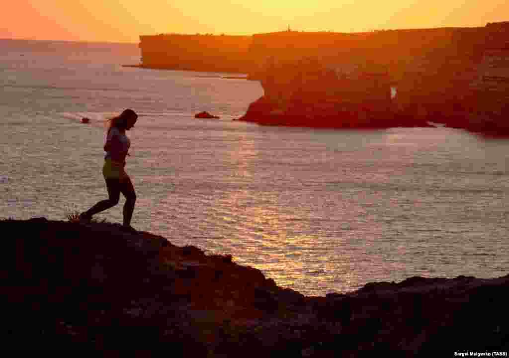 A woman jogs by the sea near the Atlesh fishing site in Crimea, Ukraine. (TASS/Sergei Malgavko)