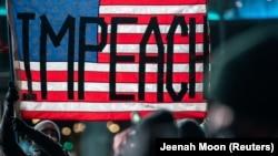 """Barclays орталығындағы """"Алып таста оны! Демократияны қорға"""" деген атаумен өткен митингі кезінде маска таққан адамдар АҚШ туын ұстап тұр. Митинг президент жақтастарының Капитолийге басып кіруіне байланысты ұйымдастырылды. Нью-Йорк, 7 қаңтар 2021 жыл."""