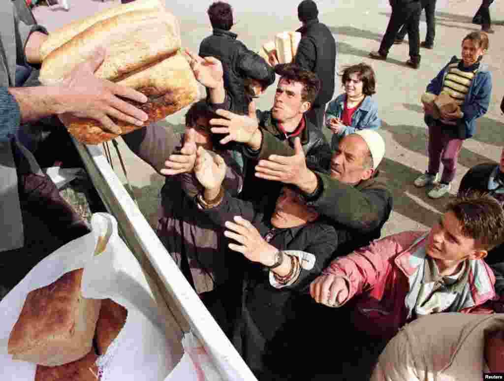 Refugjatë shqiptarë nga Kosova, duke marrë bukë në Kukës pasi kanë ikur nga luftimet që po zhvilloheshin në vendbanimet e tyre, 30 mars 1999. Arben Celi/Reuters.