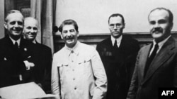 German Foreign Minister Joachim Von Ribbentrop (left), Joseph Stalin (center), and his foreign minister, Vyacheslav Molotov (right), in the Kremlin on August 23, 1939.