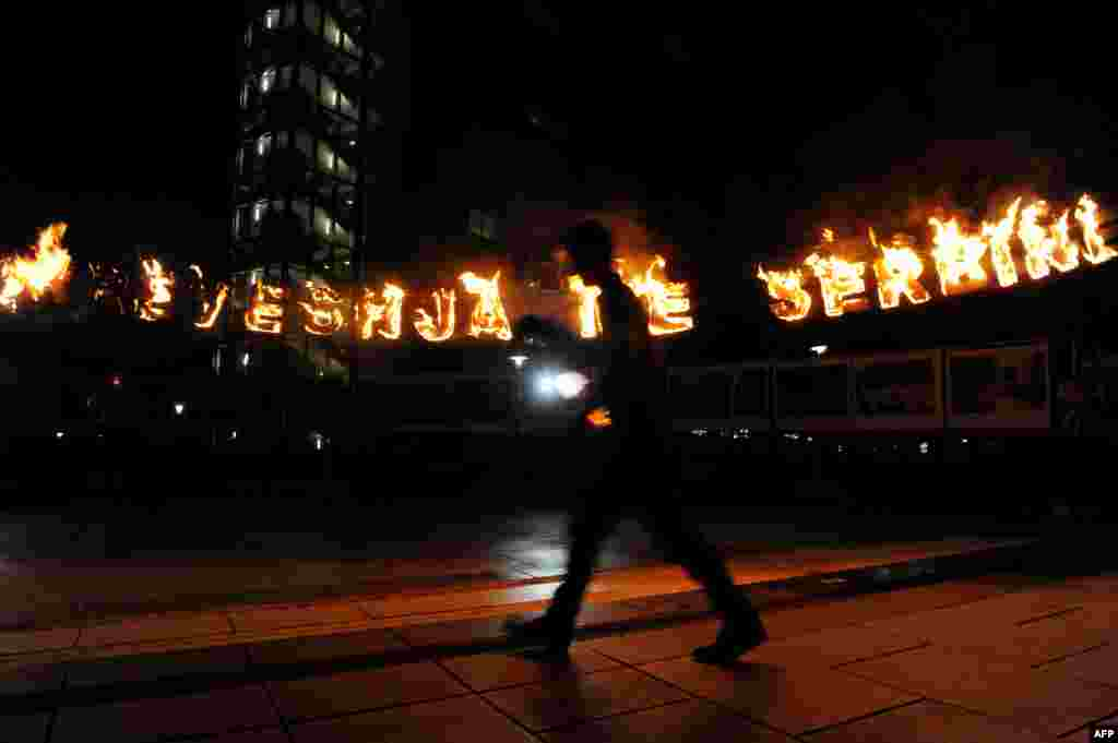 "Members of the movement Vetevendosje (Self-Determination) set letters on fire reading ""Agreement With Serbia"" in front of the Kosovar government headquarters in Pristina. (AFP/Armend Nimani)"