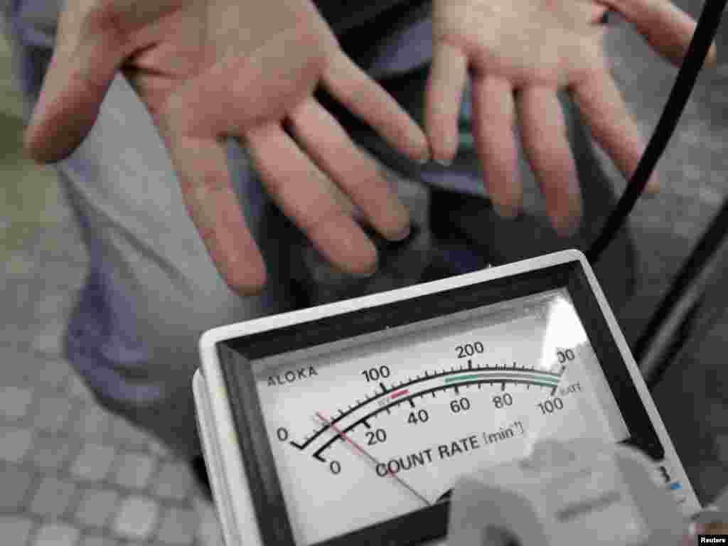La un centru de asistență socială din Yonezawa, în nordul Japoniei, la aproape o sută de kilometri de centrala nucleară Fukushima, un medic testează o fată pentru a identifica posibila contaminare cu radiații nucleare nocive, 21 martie 2011.