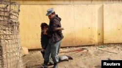 An Afghan policeman carrying his wounded comrade after a suicide car bomb attack in Kunduz province on February 10.