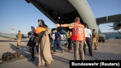 Evacuees from Afghanistan leave a German Air Force plane in Tashkent on August 26.