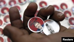 "Badges showing an image of President Muhammad Morsi and the words ""Yes To Constitution"" are displayed at a street stall in Cairo."