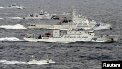 A Chinese marine surveillance ship Haijian (center) cruises next to Japanese coast guard ships in the East China Sea, near islands known as the Senkakus in Japan and the Diaoyus in China.