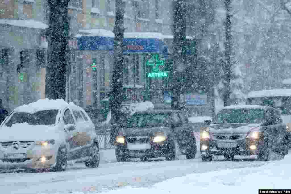 Автомобілі під час снігопаду на одній із вулиць Сімферополя в суботу, 13 лютого